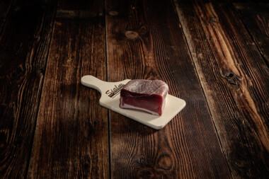 Rohnuss-Schinken auf Holzbrett Trockenfleisch Fleischtrockenerei Sialm Segnas Disentis Graubünden Tradition Spezialität Geschenk