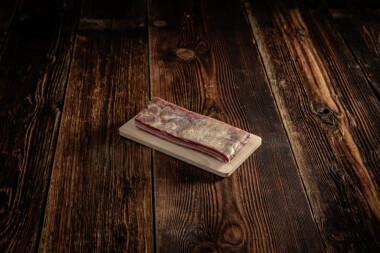 ein Stück Rohess-Speck auf Holzbrett Trockenfleisch Fleischtrockenerei Sialm Segnas Disentis Graubünden Tradition Spezialität Geschenk